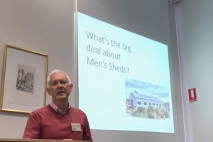 """Photo of Lynton presenting at the Library Forum with slideshow displayed in the background reading """"What's the big deal about Men's Shed?"""""""